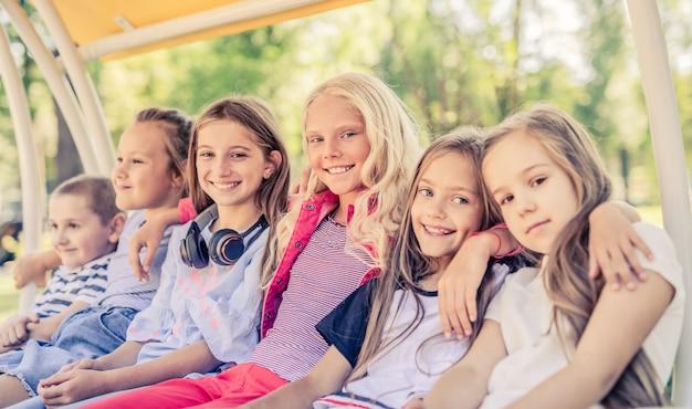 Sourire de petits amis s'asseoir sur la balançoire