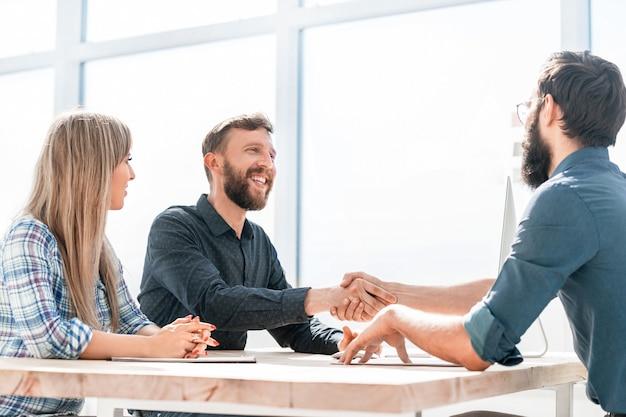 Sourire de la poignée de main des partenaires commerciaux lors d'une réunion d'affaires