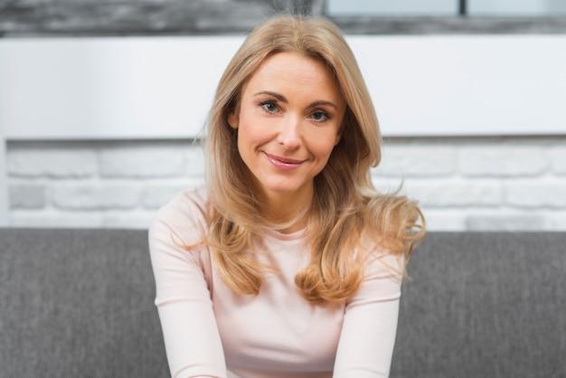 Sourire portrait d'une jeune femme blonde en regardant la caméra