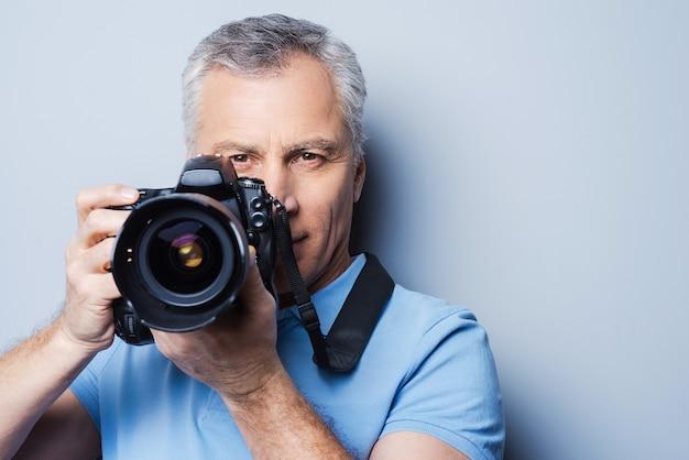 Le sourire! portrait of senior man in t-shirt holding camera en se tenant debout sur fond gris