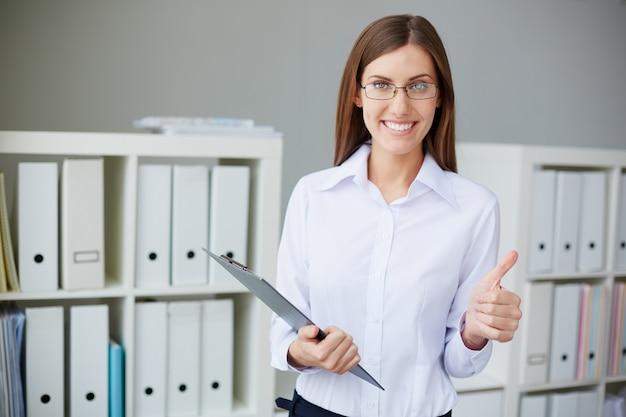Sourire secrétaire avec des lunettes et les pouces vers le haut