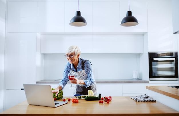 Sourire, séduisant, blond, femme aînée, dans, tablier, utilisation, ordinateur portable, pour, recette, et, boire vin
