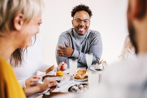Sourire séduisant homme afro-américain assis à table à manger avec des amis pour le déjeuner, souriant