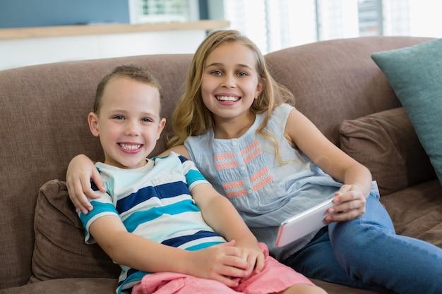 Sourire sœur et frère assis sur le canapé à l'aide de téléphone portable dans le salon à la maison