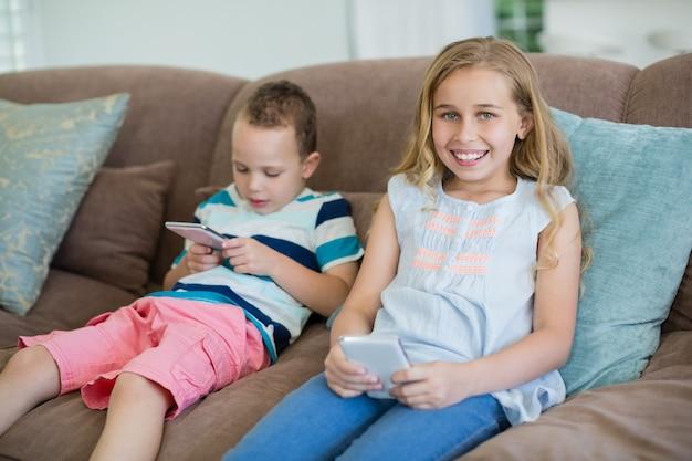 Sourire sœur et frère assis sur le canapé à l'aide de téléphone portable dans le salon