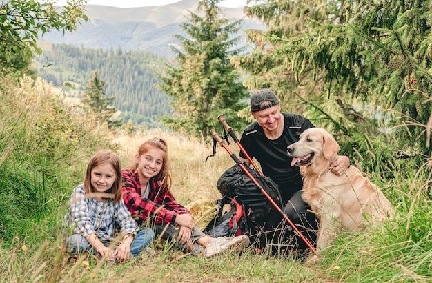 Sourire de sœurs avec père au repos pendant la randonnée en montagne