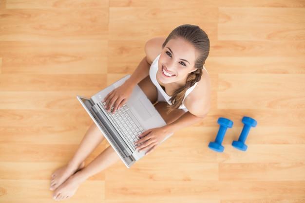Sourire sportif brune à l'aide d'un ordinateur portable et assis à côté d'haltères