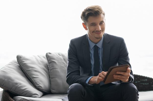 Sourire succès jeune homme utiliser l'ordinateur tablette