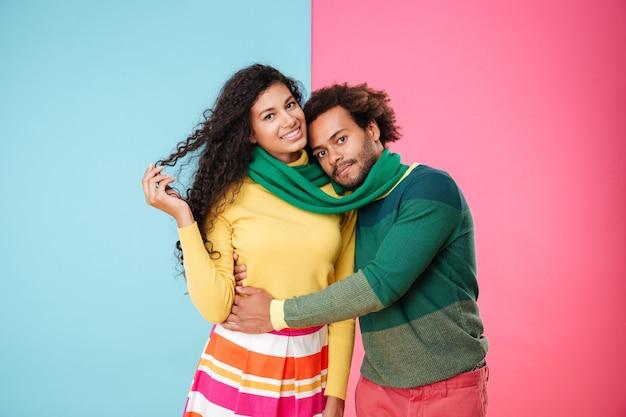 Sourire tendre jeune couple en écharpe debout et embrassant
