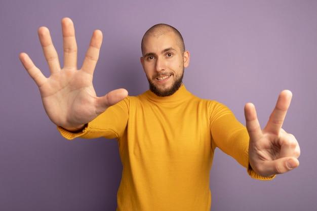 Sourire tout droit jeune beau mec montrant différents nombres isolés sur violet