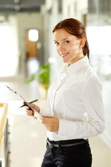 Sourire travailleur tenant un stylo et un presse-papiers