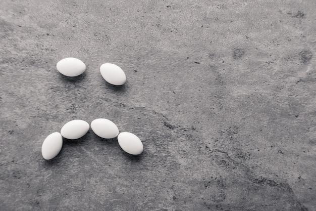 Sourire triste de pilules de médecine blanches dispersées