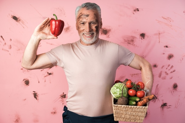 Sourire, vieil homme tient un panier de légumes et tient un poivron rouge dans son autre main