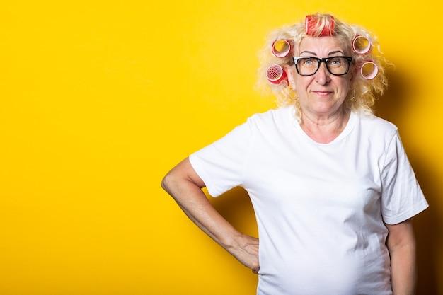 Sourire vieille femme avec des bigoudis dans un t-shirt blanc sur une surface jaune
