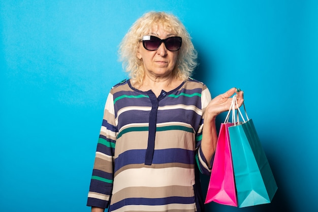 Sourire vieille femme tenant des sacs à provisions sur le mur bleu.