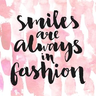 Les sourires sont toujours à la mode citation inspirante pour la calligraphie d'affiches et de cartes sur rose