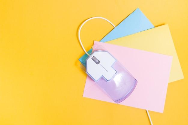Souris d'ordinateur et enveloppes papier de couleur sur fond jaune,