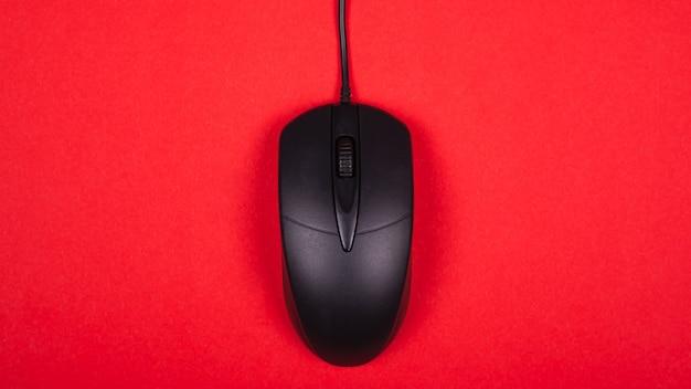 Souris d'ordinateur noir sur fond rouge vue de dessus.