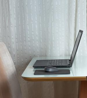 Une souris et un ordinateur sous la table blanche près de la chaise