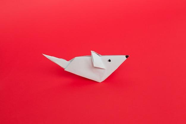 Souris à papier origami blanc sur fond rouge.
