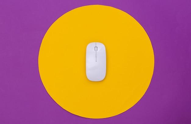 Souris pc blanche sur fond violet avec cercle jaune. prise de vue en studio conceptuel. minimalisme. vue de dessus
