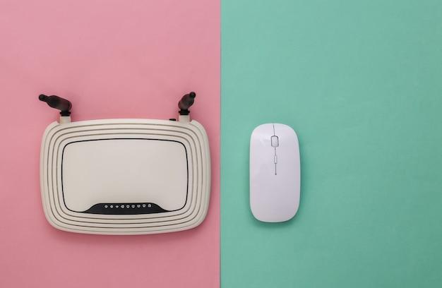 Souris pc moderne avec routeur wi-fi sur fond pastel bleu rose. prise de vue en studio. vue de dessus. mise à plat