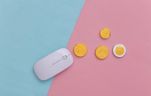 Souris pc avec pièces de monnaie sur fond pastel bleu-rose. business en ligne. vue de dessus. minimalisme
