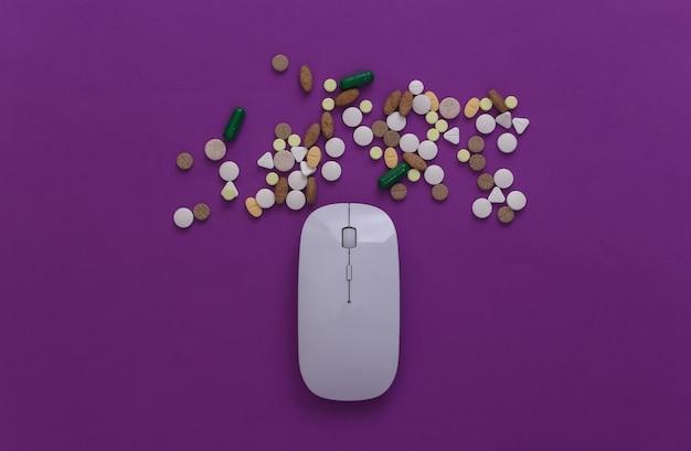 Souris pc avec pilules sur fond violet. vue de dessus. mise à plat