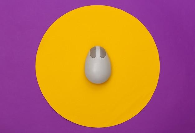 Souris pc rétro sur fond violet avec cercle jaune. prise de vue en studio conceptuel. minimalisme. vue de dessus