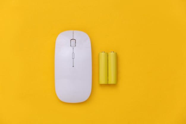 Souris pc sans fil et deux batteries sur fond jaune. vue de dessus