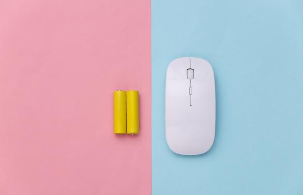 Souris pc sans fil et deux piles sur fond pastel bleu-rose. vue de dessus