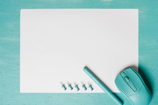Souris; stylo et punaises sur papier blanc sur fond turquoise