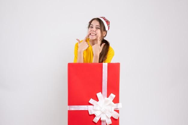 Sourit jeune fille avec bonnet de noel debout derrière gros cadeau de noël sur blanc
