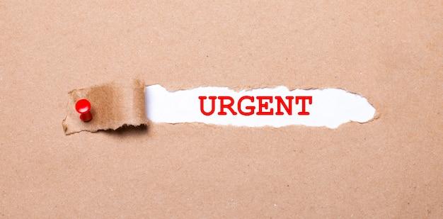 Sous la bande déchirée de papier kraft attachée avec un bouton rouge se trouve un papier blanc intitulé urgent