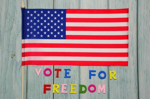 Sous le drapeau américain, le texte vote pour la liberté est bordé de lettres multicolores sur un fond en bois