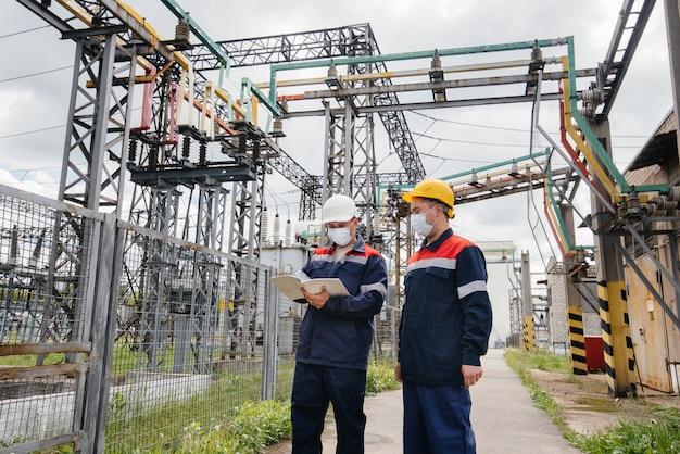 Les sous-stations électriques des ingénieurs effectuent une enquête sur les équipements modernes à haute tension dans le masque au moment de la pandémie. énergie. industrie.