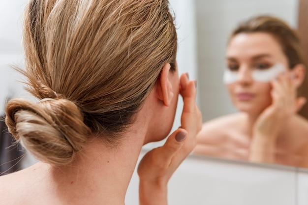 Sous le traitement des poches sous les yeux, réflexion du miroir flou