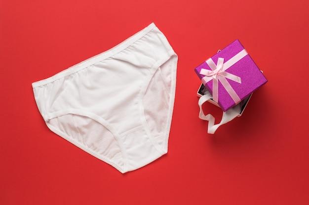 Sous-vêtements blancs pour femmes et coffret cadeau sur une surface rouge. mise à plat.