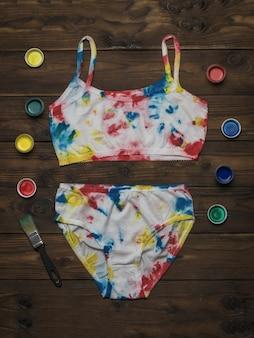 Sous-vêtements pour femmes peints dans le style tie dye et un ensemble de peintures sur une table en bois sombre.