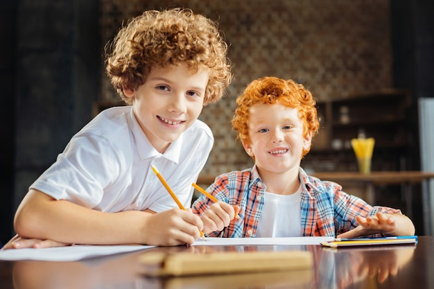 Le soutien est ce qui compte vraiment. des frères sympathiques aiment passer du temps ensemble et sourire largement devant la caméra tout en dessinant avec des crayons colorés.