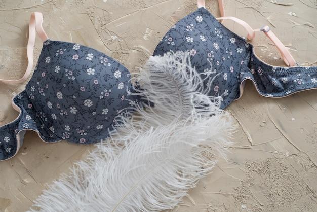 Soutien-gorge bleu isolé sur un fond de béton. coton délicat et plumes blanches