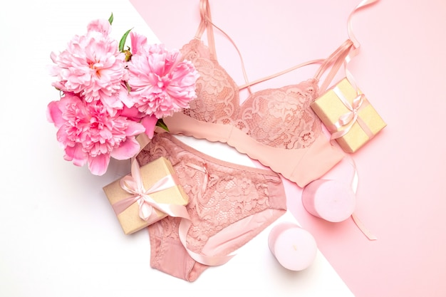 Soutien-gorge et culotte femme en dentelle rose élégante, bougies roses fleurs, un bouquet de belles pivoines, cadeaux