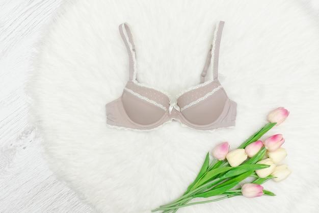 Soutien-gorge en dentelle beige sur fourrure blanche. tulipes roses. à la mode .