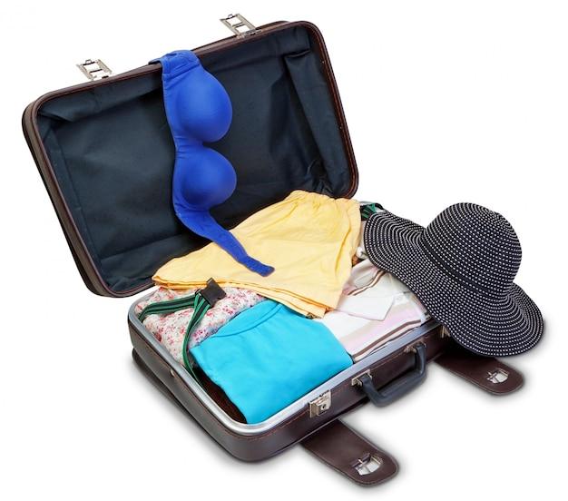Soutien-gorge et panama sur une valise pour des vacances. sur un mur blanc.