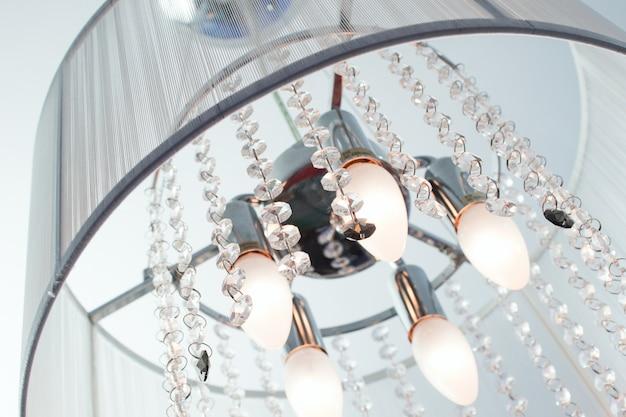 Souvent, les lustres d'inclusion avec des cristaux et un abat-jour en tissu au plafond