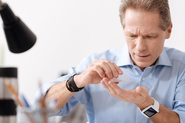 Soyez attentif. personne de sexe masculin très intentionnelle portant une chemise bleue ayant un bracelet en cuir et des montres intelligentes tout en versant des pilules