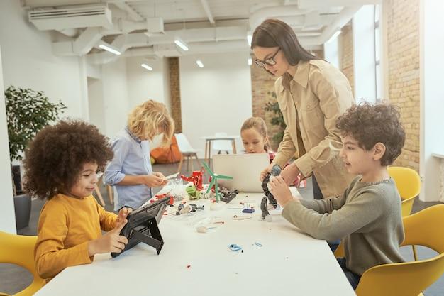 Soyez familiarisé avec la technologie, des enfants divers assemblent et programment des robots pendant la classe de tige avec