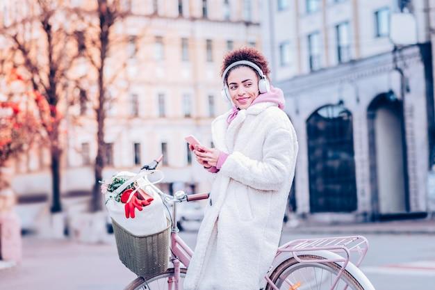 Soyez heureux. fille ravie s'appuyant sur le vélo tout en ayant une pause pendant la marche