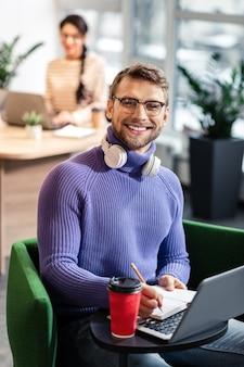 Soyez heureux. gentil homme brune exprimant la positivité tout en regardant directement la caméra