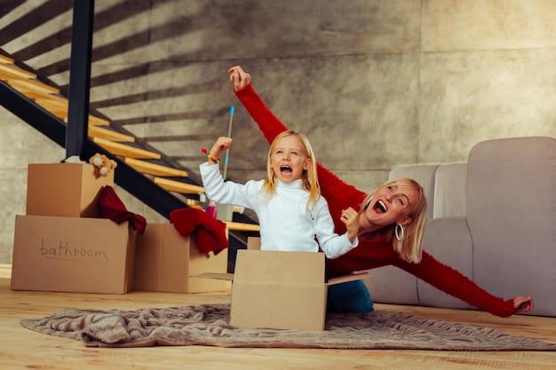 Soyez heureux. heureux enfant blond ouvrant la bouche en riant d'une blague